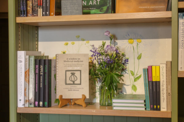 A shelf containing books on gardening and nature