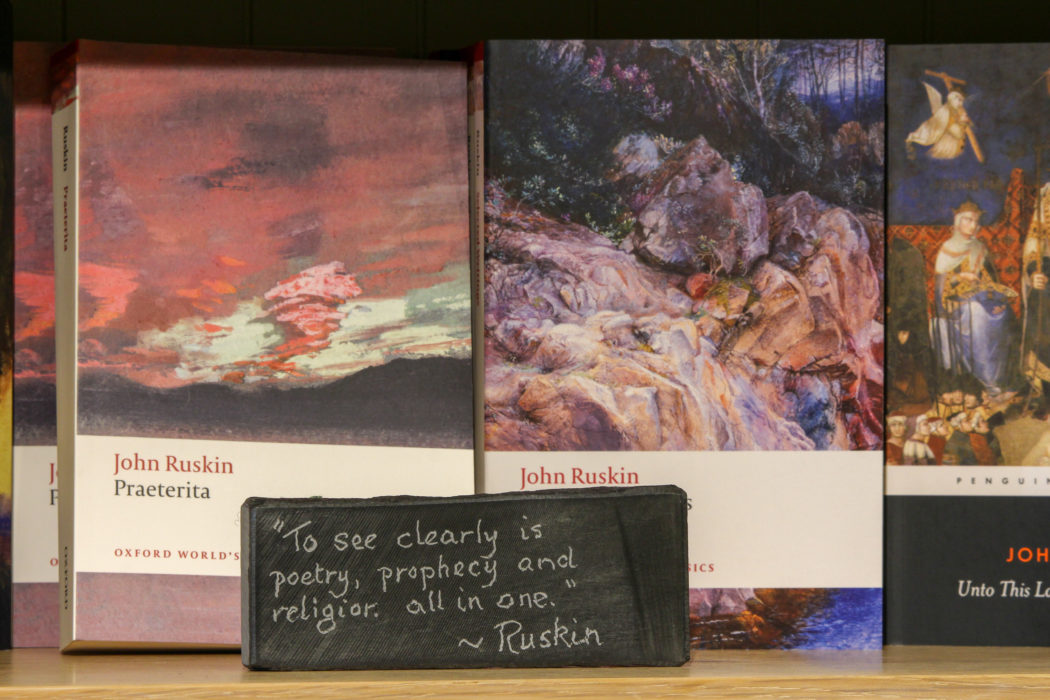 A collection of Ruskin books, behind a blackboard featuring a Ruskin quote
