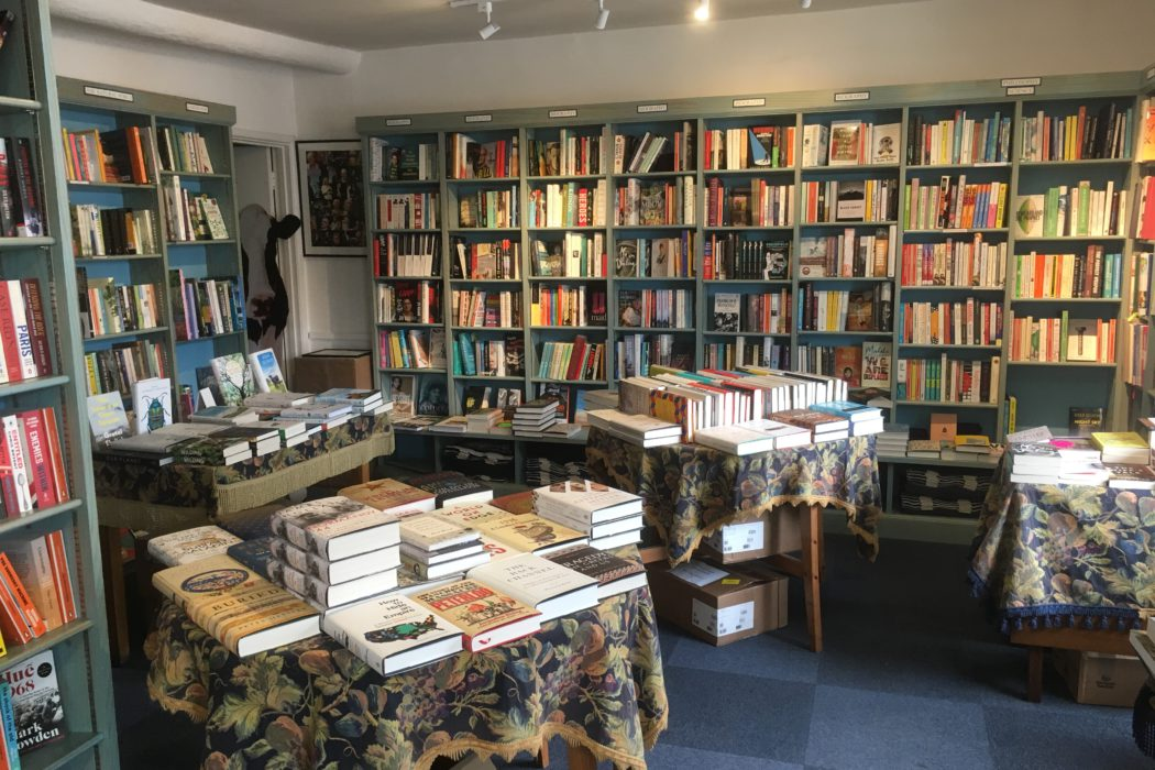 View across to Aldeburgh Bookshop's biography section with a cow peering out of the stock cupboard