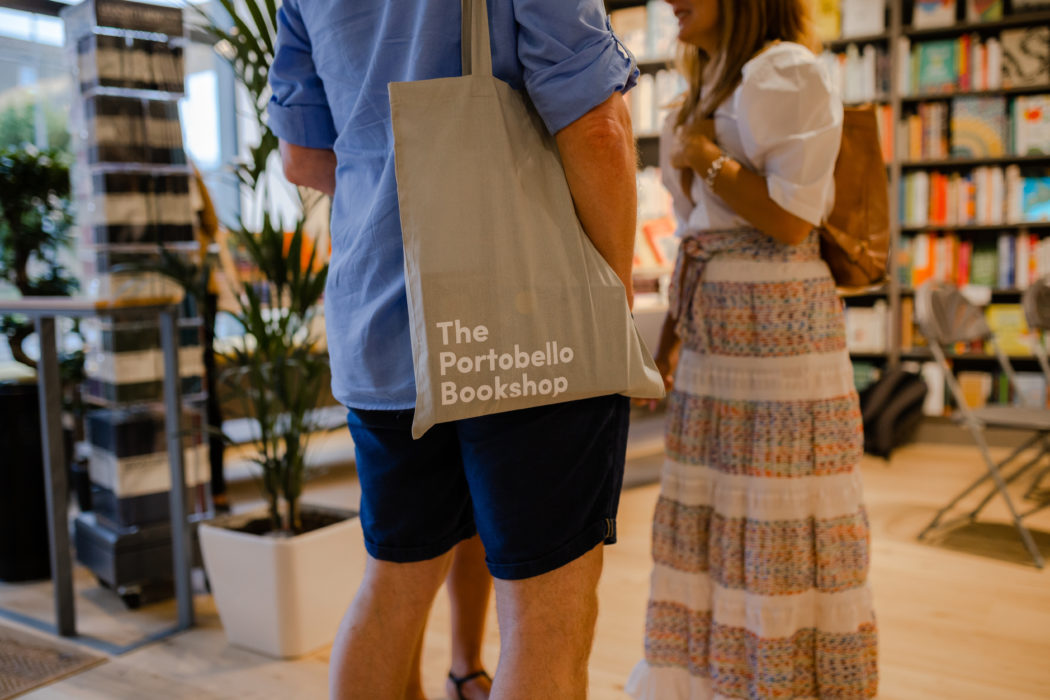 A customer stands with a Portobello Bookshop tote bag over his shoulder