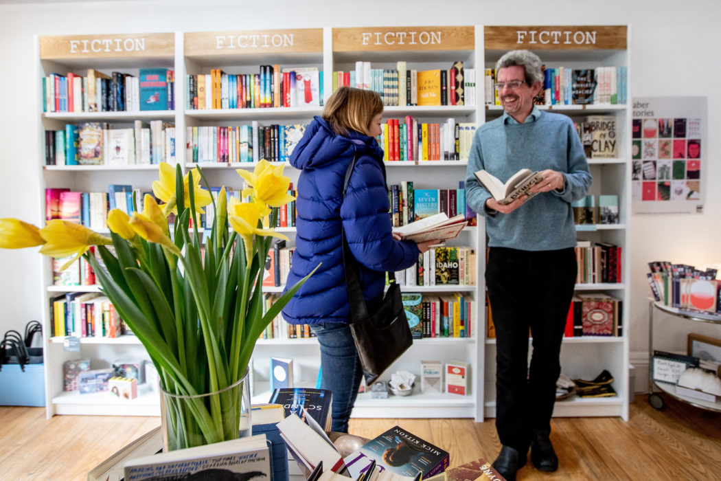 Two customers look around the Little Ripon Bookshop; there are daffodils on the table in front of them