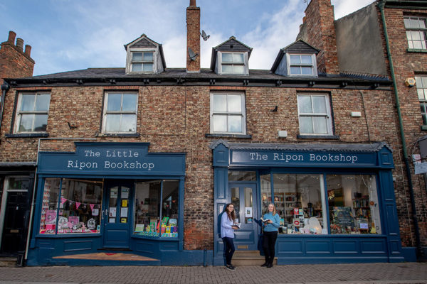 Two employees stand outside the Little Ripon Bookshop